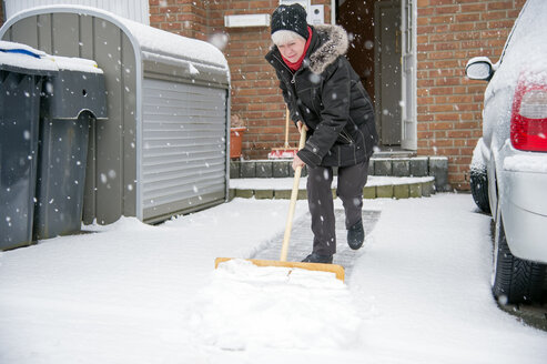 Germany, Grevenbroich, woman shoveling snow in front of house - FRF000188