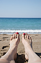 Greece, Peloponnese, woman's feet on the beach - CHPF000012