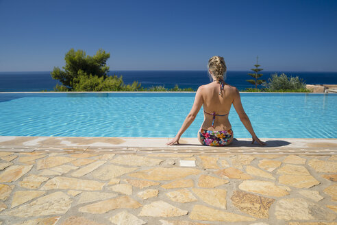 Greece, Peloponnese, woman sitting at pool edge looking at the sea - CHPF000016