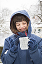 Portrait of smiling girl with cup of tea in winter - LVF002720