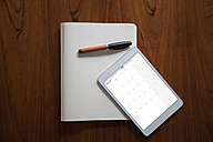 Digital tablet and ballpen lying on opened notebook - RBF002432