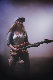 Woman playing with toy guitar - VE000024