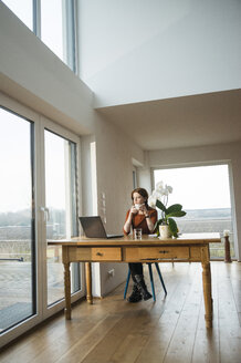 Young woman with laptop at wooden table looking out of window - UUF003203