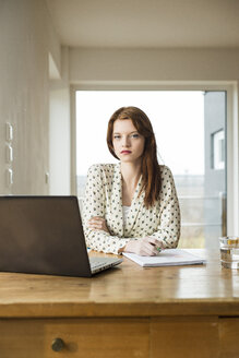 Young woman with laptop at wooden table - UUF003207