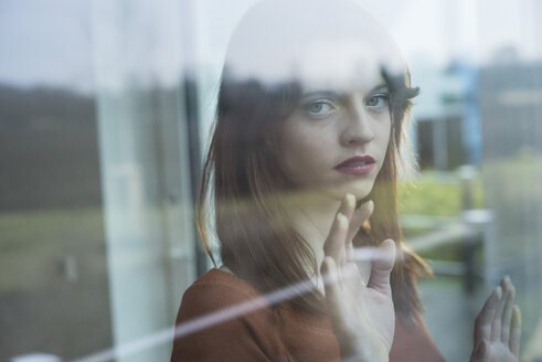 Serious young woman behind windowpane - UUF003223
