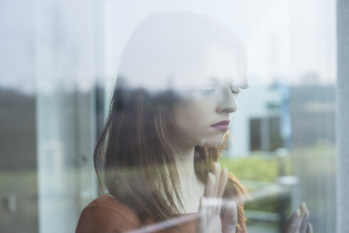 Serious young woman behind windowpane - UUF003225