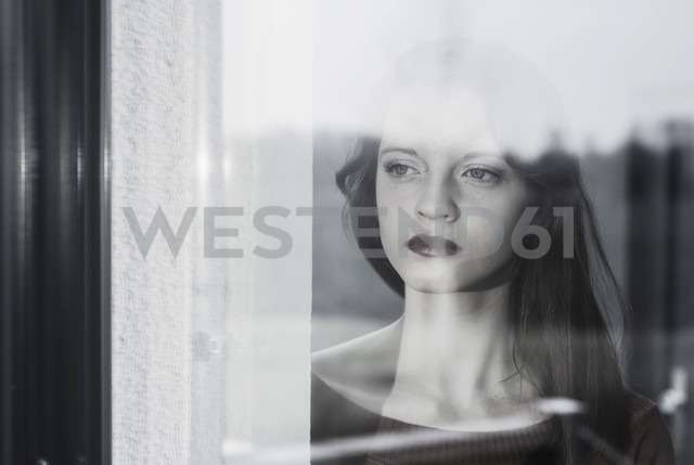 Serious young woman behind windowpane - UUF003229