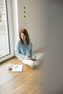 Young woman sitting on floor taking notes - UUF003232