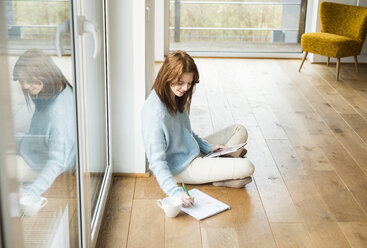 Young woman sitting on floor taking notes - UUF003233