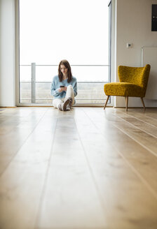 Young woman sitting on floor using cell phone - UUF003236
