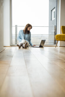 Young woman sitting on floor using laptop - UUF003249