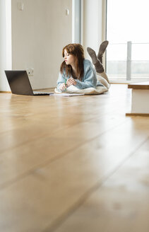 Young woman lying on floor using laptop - UUF003250