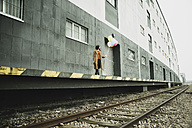 Young woman with suitcase holding bunch of balloons on platform - UUF003263