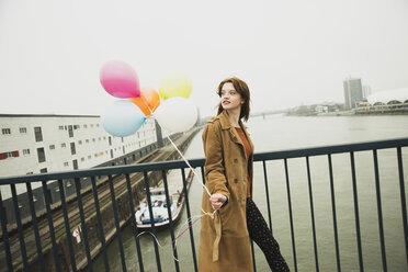 Young woman on bridge holding bunch of balloons - UUF003271