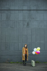 Young woman with suitcase holding bunch of balloons - UUF003274