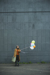 Young woman with suitcase holding bunch of balloons - UUF003277