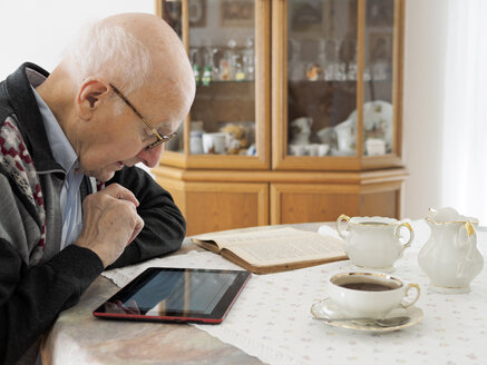 Old man sitting at table using digital tablet - LAF001309