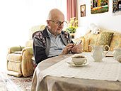 Old man sitting at table using cell phone - LAF001313