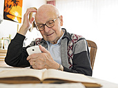 Old man sitting at table using cell phone - LAF001315