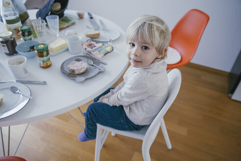 Little boy sitting at breakfast table looking up - MFF001462
