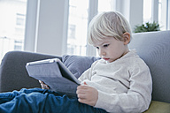 Little boy sitting on the couch watching something on digital tablet - MFF001464