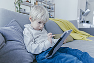 Little boy sitting on the couch playing with digital tablet - MFF001466