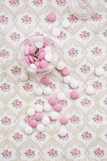Glass of pink and white chocolate buttons on floral patterned cloth - LVF002740