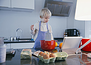Little boy standing in the kitchen baking with help of digital tablet - MFF001472