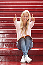 Portrait of smiling female teenager showing thumbs up - WWF003758