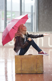 Austria, Thalgau, teenage girl with red umbrella sitting on her suitcase in the rain - WWF003768