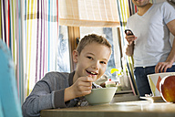 Portrait of smiling boy sitting at breakfast table with granola - PDF000744
