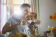 Father and son sitting at breakfast table taking a selfie - PDF000750