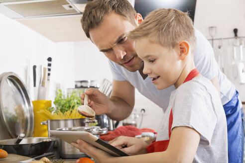 Father and son cooking together using digital tablet - PDF000764