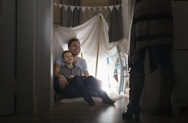 Woman discovering husband and son in self-made tent at home - PDF000762