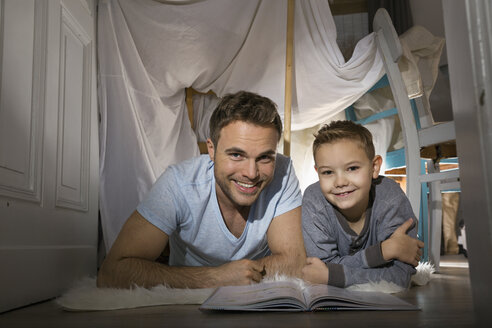 Father and son with book lying on the floor in self-made tent at home - PDF000723