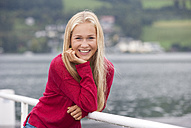 Austria, Mondsee, portrait of smiling teenage girl wearing red pullover - WWF003782