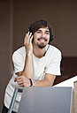 Portrait of young man hearing music with headphones - WWF003705