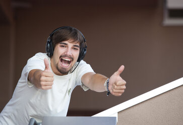 Portrait of young man with headphones showing thumbs up - WWF003706