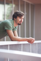 Portrait of young man leaning on railing - WWF003707