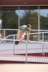 Young man jumping over railing - WWF003708