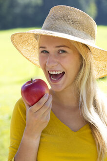 Portrait of smiling teenage girl eating an apple - WWF003814