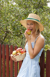 Portrait of smiling teenage girl eating an apple - WWF003825
