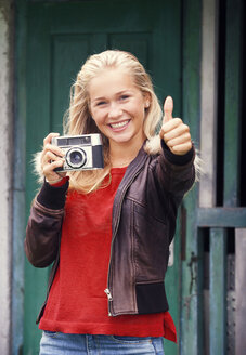 Portrait of smiling teenage girl with old camera and thumb up - WWF003791
