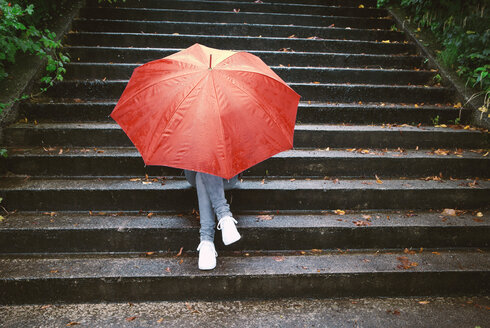 Teenage girl sitting on stairs hiding behind red umbrella - WWF003792