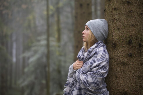 One female teenager with blanket and hat leaning on tree trank - WWF003793