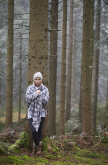 Austria, sad female teenager leaning at tree trunk in autumn - WW003794