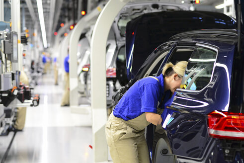 Production of VW cars in a factory, worker installing vehicle interior - SCH000459