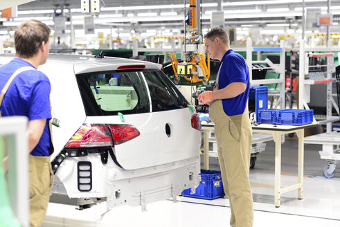Production of VW cars in a factory, workers installing rear lights - SCH000461