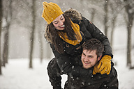 Young man giving his girlfriend a piggy back - PAF001253