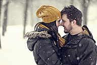 Happy young couple head to head in winter - PAF001259